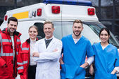 Photo happy ambulance doctors working team standing in front of car
