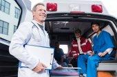 Lächelnde Sanitäter arbeiten mit Krankenwagen zusammen