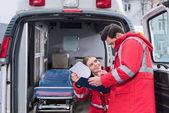 Fotografie glücklich männlicher und weiblicher Sanitäter Lesen von Dokumenten vor Krankenwagen