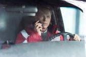 Ernsthafter Sanitäter sitzt im Krankenwagen auf dem Fahrersitz und spricht per Mobilfunk