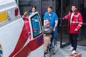 Ärzte verhelfen Rollstuhlfahrer zum Krankenwagen