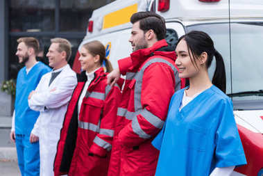 ambulance doctors working team standing and posing in front of car