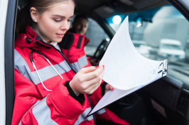 female paramedic sitting in ambulance and looking at clipboard