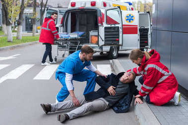 doctors helping injured man lying on a street