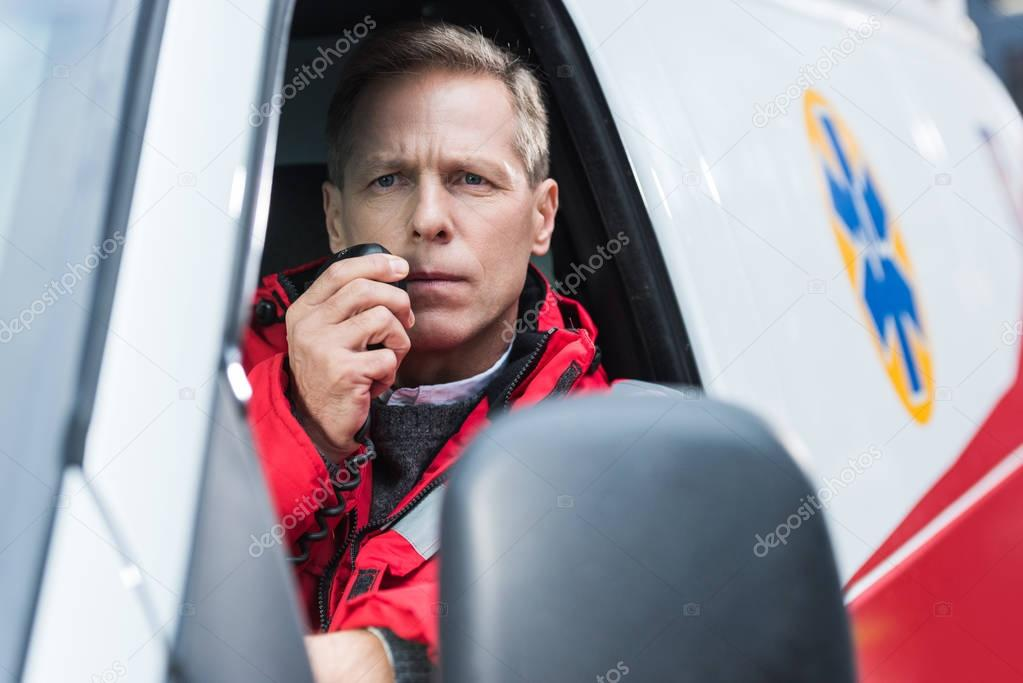 handsome middle aged paramedic talking by portable radio