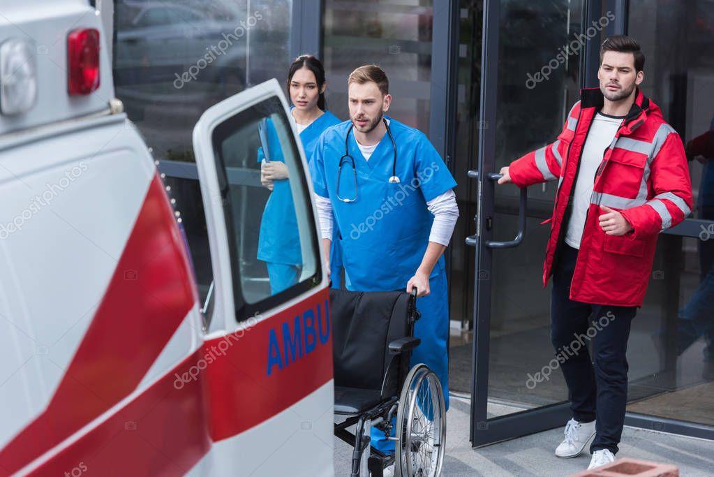 paramedics moving wheelchair from hospital to ambulance
