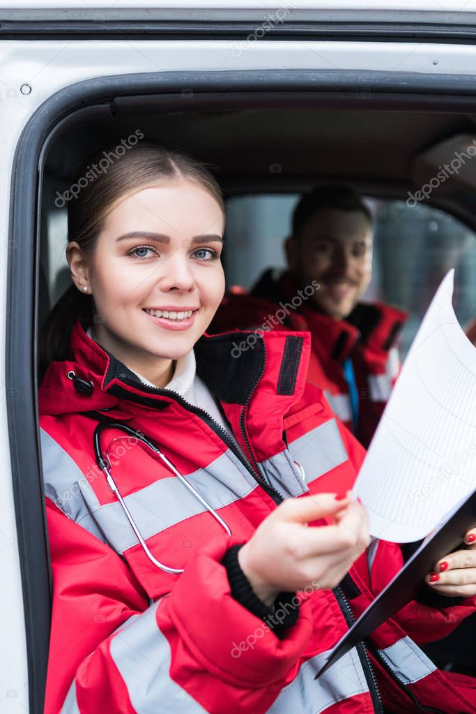 smiling young female paramedic holding clipboard and looking at camera