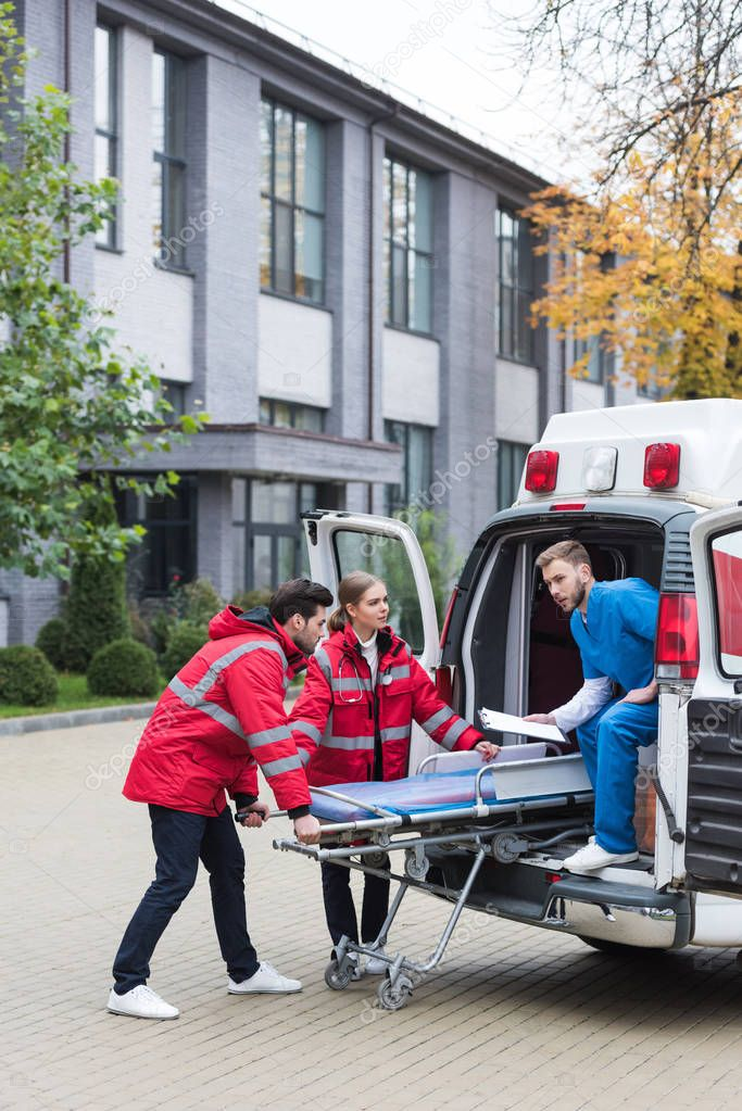 paramedics moving ambulance stretcher into car