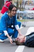 Fotografie mladá lékařka asijské pomáhá bezvědomí zraněný muž ležel na ulici