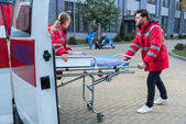 Photo doctors taking ambulance stretcher to help wounded man