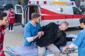 Fotografie mladí zdravotníci pomáhají zraněný muž Lehněte si na sanitní nosítka