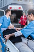 Fotografie mladí zdravotníci přesun raněného na sanitní nosítka