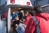 Photo team of paramedics moving wounded mature man into ambulance