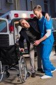 Sanitäter helfen verletztem Patienten im Rollstuhl zu sitzen