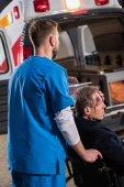 záchranáře pohybující se zraněný zralý muž na invalidním vozíku na ambulanci