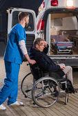 Photo paramedic moving injured man on wheelchair to ambulance