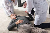 cropped image of doctor checking unconscious middle aged man palpitation with stethoscope