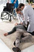 medico femminile che controlla la palpitazione uomo incosciente con lo stetoscopio