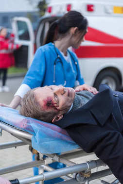 female doctor moving wounded mature man on ambulance stretcher