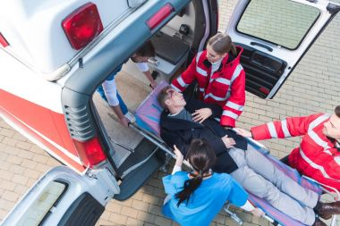 overhead view of paramedic team moving injured man on ambulance stretcher into car