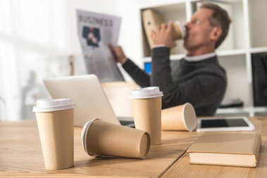 businessman drinking coffee with scattered disposable coffee cups on foreground