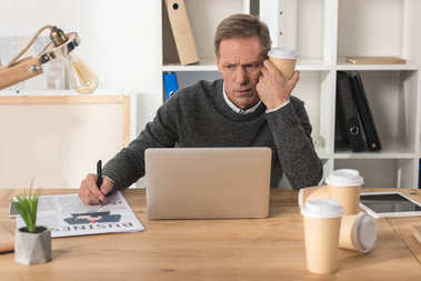 tired businessman sitting at laptop with disposable coffee cup