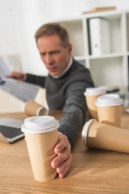 tired middle aged businessman taking one more disposable coffee cup