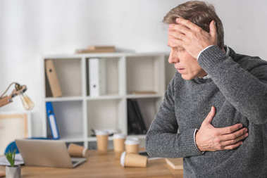 middle aged man having headache and heart attack