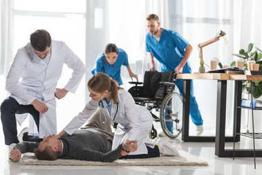 young doctors checking pulse of unconscious man lying on a floor in hospital