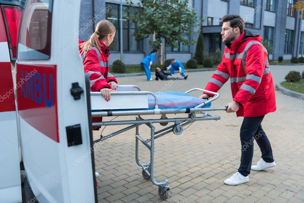 doctors taking ambulance stretcher to help wounded man