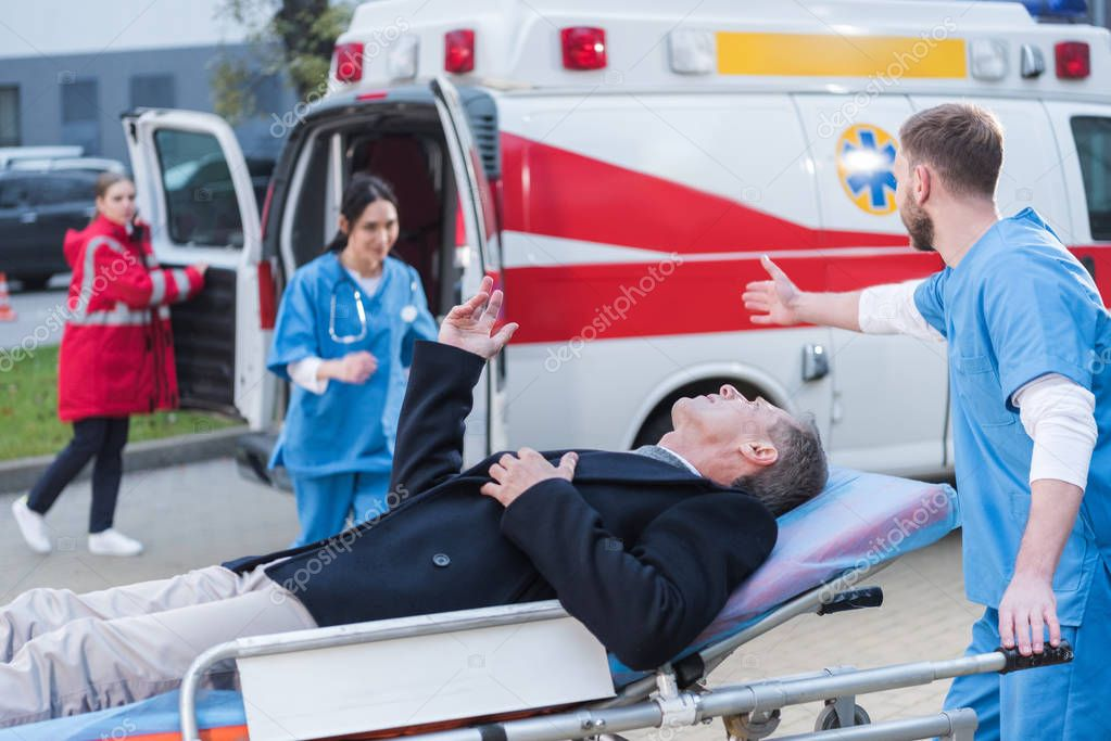 injured man and doctor asking help of other paramedic