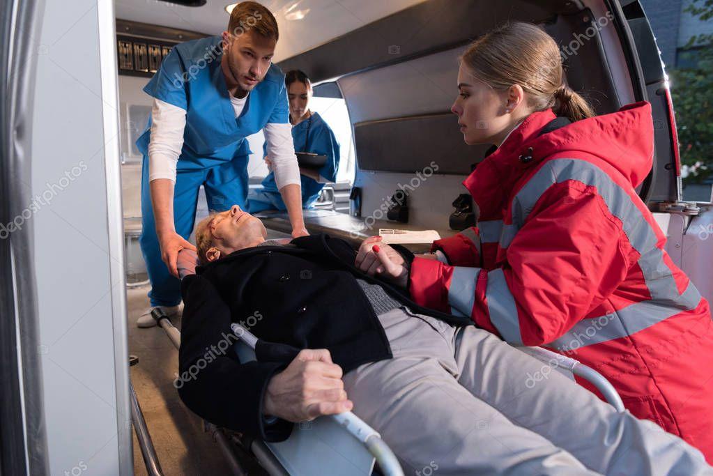 paramedics moving wounded mature man into ambulance on stretcher