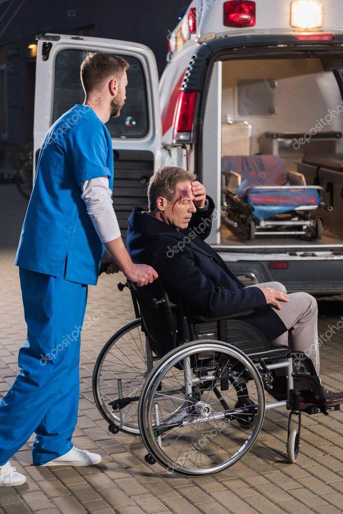 paramedic moving injured man on wheelchair to ambulance