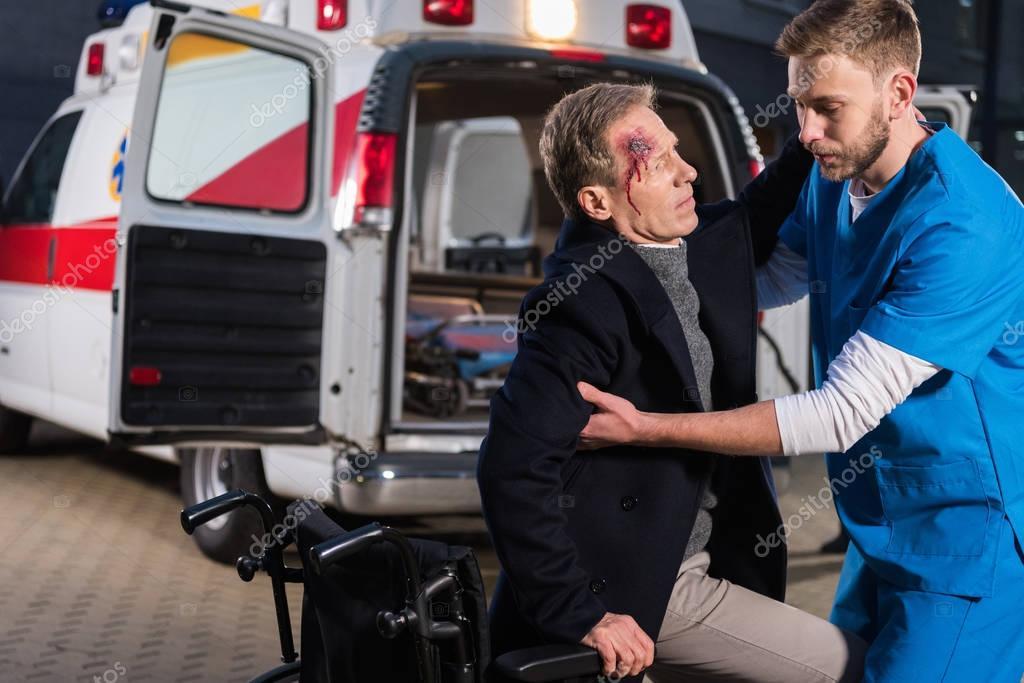 paramedic helping injured man to sit on wheelchair