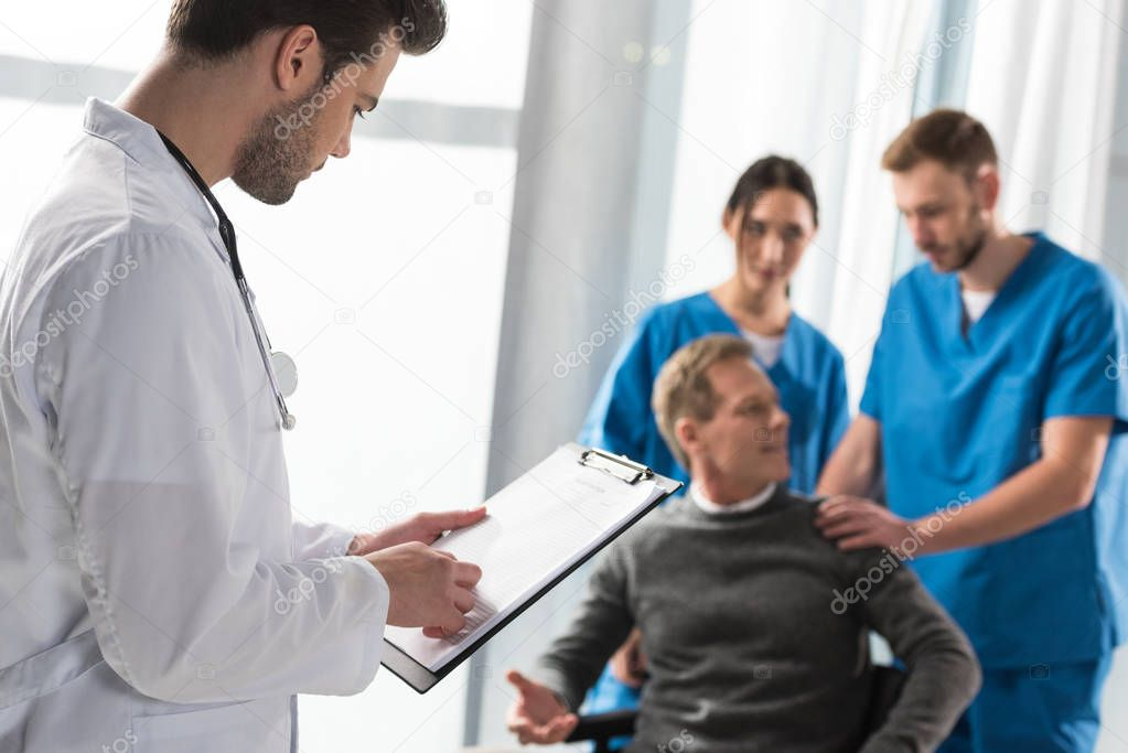 doctor looking at patient medical book in hospital