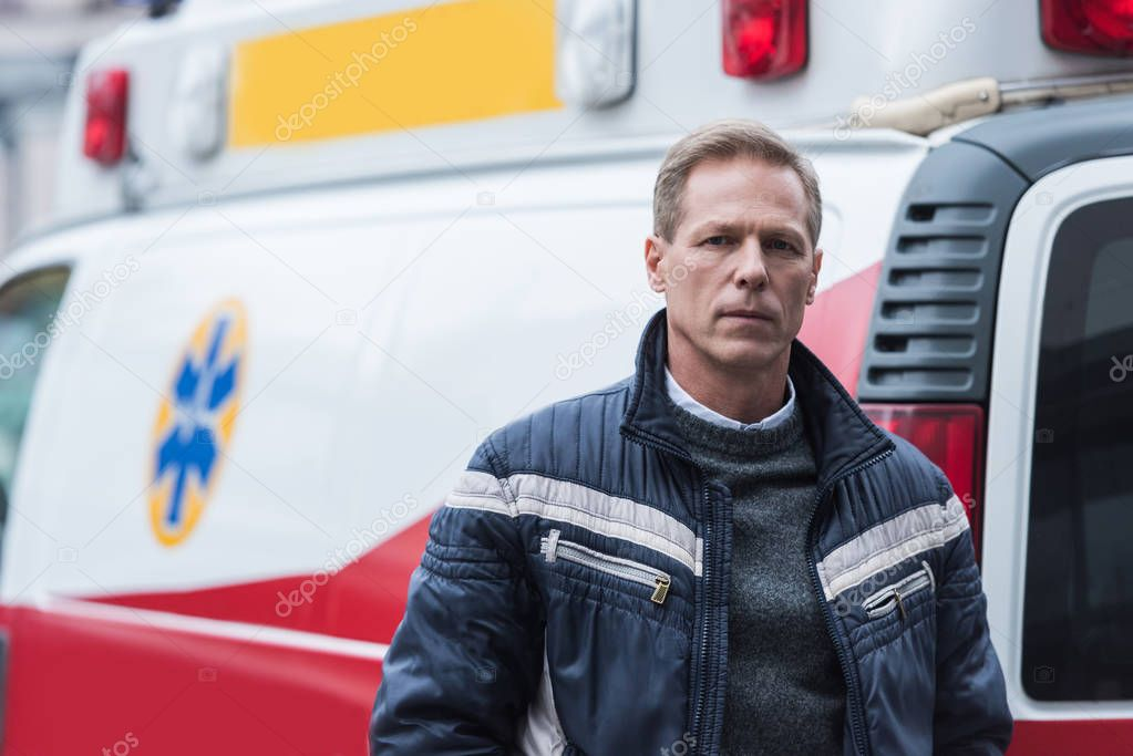 paramedic in casual clothes standing in front of ambulance and looking at camera