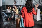 Fényképek nő, bevásárló táskák megy a kávézó barátai