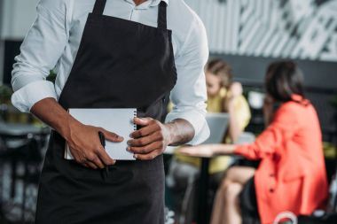 cropped shot of waiter in apron with notepad at cafe