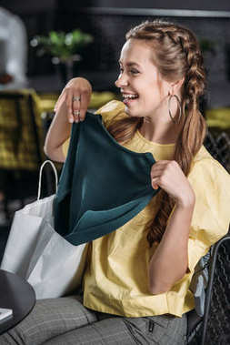 young happy woman getting out new dress from shopping bag