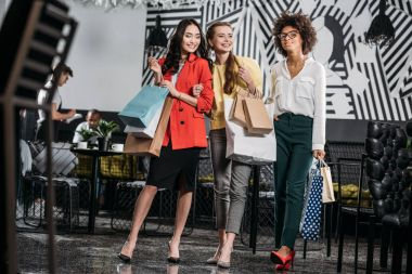 group of young women with shopping bags in cafe