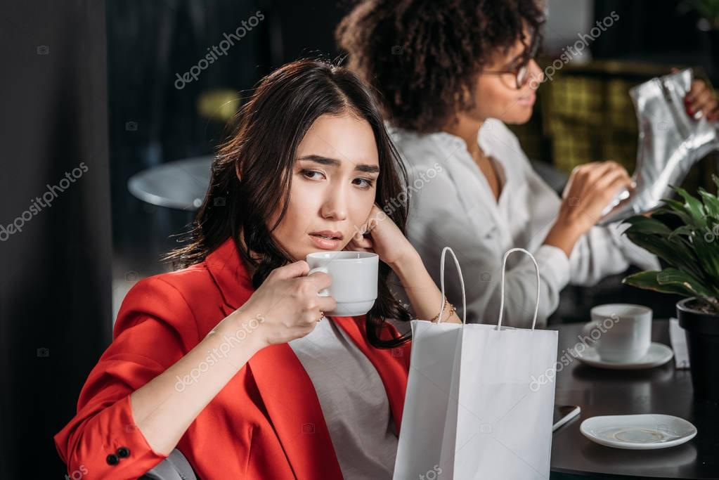 depressed young woman drinking coffee after shopping