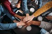 top view of people making team gesture in cafe