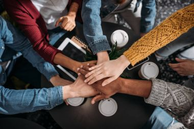 top view of people making team gesture in cafe