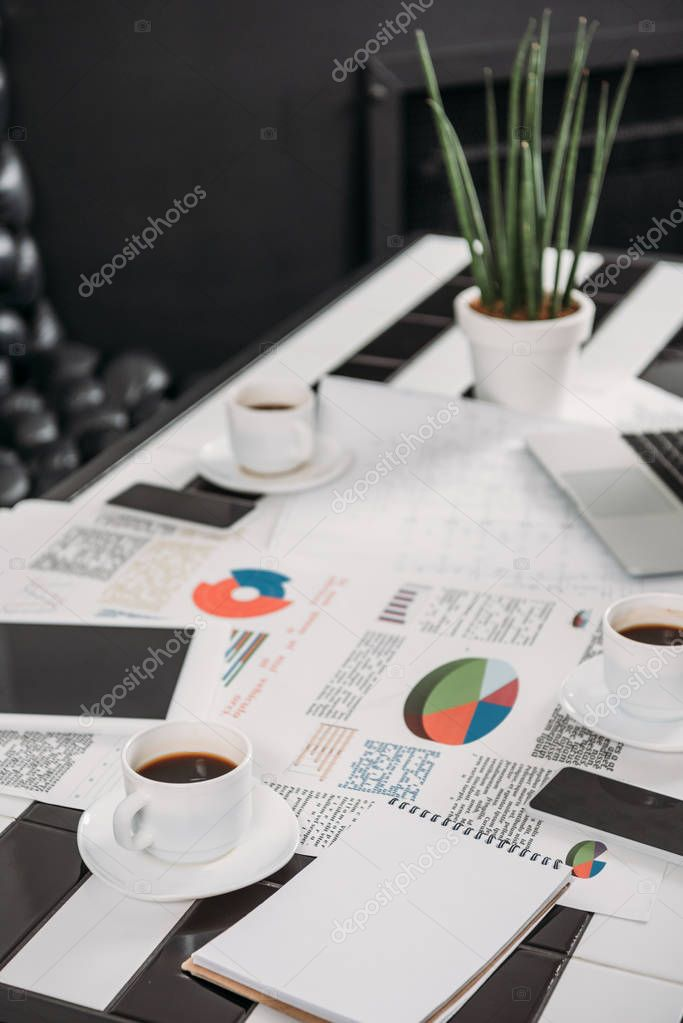business documents on workplace with digital devices and coffee