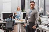 névtábla és planchette-modern irodában boldog afro-amerikai ember