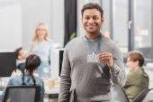 Fotografia uomo afroamericano felice che Mostra nome tag presso ufficio moderno
