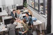 Veselá multikulturní obchodní tým provedení zásobníku rukou v moderní kanceláři