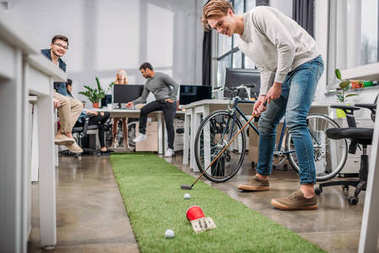 happy people playing in mini golf at modern office