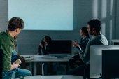 Menschen, die abends im Büro die Präsentation verfolgen. leerer Bildschirm