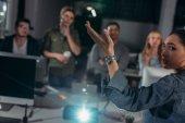 Fotografie junge Leute sehen Präsentation in modernem Büro, Frau zeigt auf Bildschirm